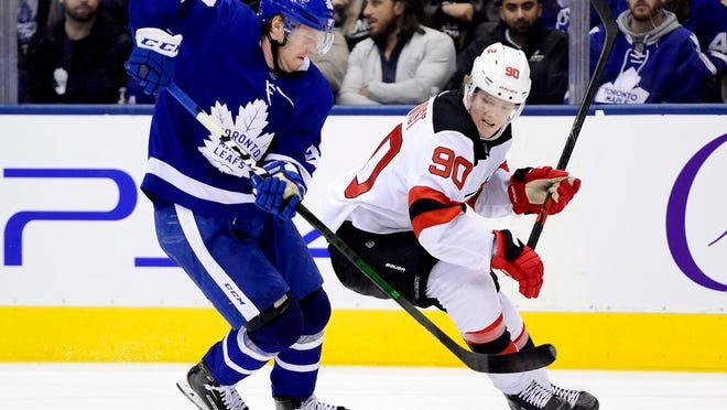 Toronto Maple Leafs defenseman Rasmus Sandin (38) and New Jersey Devils center Jesper Boqvist (90) vie for control of the puck during the third period of an NHL hockey game Tuesday, Jan. 14, 2020, in Toronto.