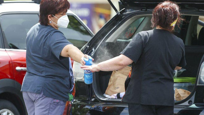 An employee of St. Mark Village sprays a coworker with Lysol in the parking lot of the nursing home Monday in Palm Harbor.