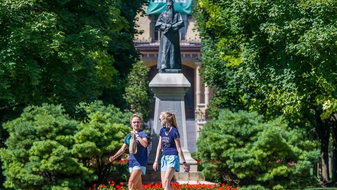 Unmasked sudents walk on campus of the University of Notre Dame on Tuesday, Aug. 18, 2020, in South Bend, Ind.