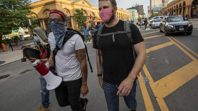 Right to left, Ryan McMullen, a veteran of the Afghanistan war, walks up High Street with Jordan M., no last name given, and Jorge Tony during a protest in the Short North on Friday.