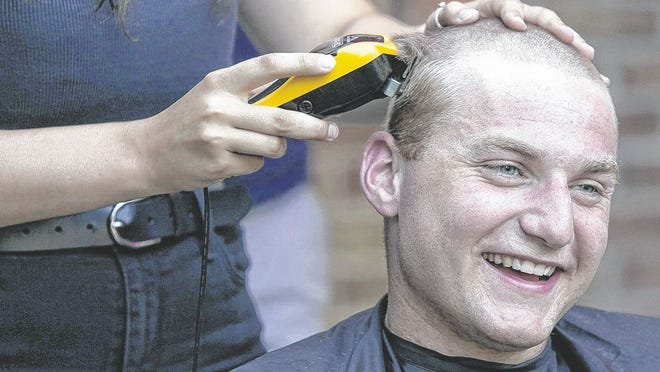 Spencer White, a 2020 graduate of Pickerington High School North, laughs as he receives a buzz haircut during a party July 8. White earned an appointment to the United States Military Academy at West Point in New York. Because of the COVID-19 coronavirus pandemic, some of the traditions for new cadets have been altered, including the head-shaving ceremony.