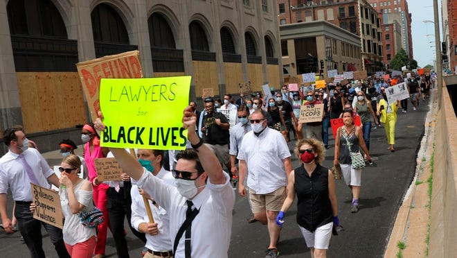 Lawyers with the Missouri Public Defenders stage a protest march in support of Black Lives Matter on Monday, June 8, 2020, through downtown St. Louis, with about 100 colleagues, staff and supporters. The group marched from from the appellate courthouse to the the Thomas F. Eagleton U.S. Courthouse, where they staged an 8-minute, 46-second die-in on the courthouse plaza.