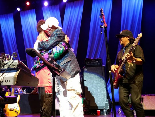 Sly Stone embraces  Alex Davis while Blaise Sison smiles