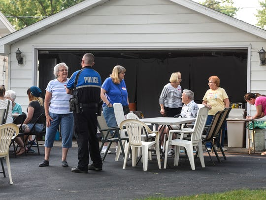 People gather in front of the home of Ginny and George Jacobs during National Night Out events Tuesday, Aug. 1, in St. Cloud.