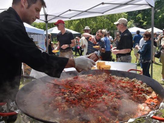 Scott McEvoy of McEvoy's Culinaria in Sister Bay adds finishing spice to his chicken and chorizo paella at last year's Uncork Summer. The Culinaria is scheduled to be back for this year's festival.