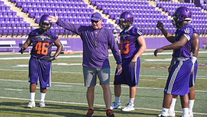 Northwestern State defensive coordinator Daryl Daye talks with linebackers Shawn Stephens and Peyton Guidry.