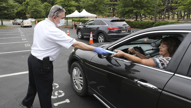 Members of the Tuscaloosa COVID-19 incident command team pass out masks during a drive-thru distribution at the Tuscaloosa Amphitheater Tuesday, July 7, 2020. Fire Chief and Incident Commander Randy Smith passes masks to a motorist.