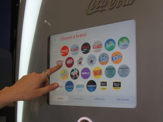"The manager of the Cavern 6 Theater, illustrates how the theater's new ""free-style"" soda machine works."