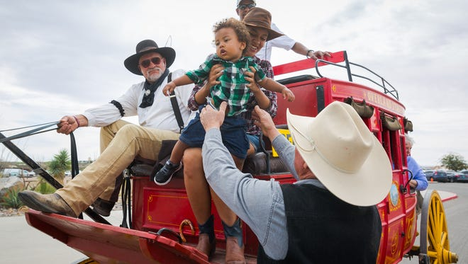 Pete Paulson, left, holds four horse's reins steady as Vernon Casados, right, helps Chaelene Smith and one-year-old Cameron Belle dismount a stagecoach during the 17th-Annual Cowboy Days at the New Mexico Farm & Ranch Heritage Museum March 5, 2016.