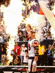 J.J. Watt walks onto the field with a  flag before the Houston Texans' game against the Jacksonville Jaguars at NRG Stadium.