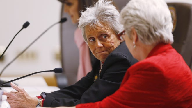 Rep. Joann Ginal, center, D-Fort Collins, and Rep. Lois Court, right, D-Denver, confer while Dr. Michelle Stanford, background testifies during a legislative hearing on the two representatives' proposal that would give dying patients the option to seek help ending their lives Friday, Feb. 6, 2015, in Denver.