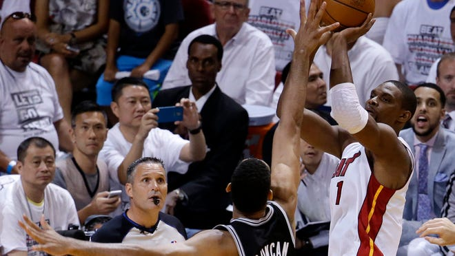 Miami Heat center Chris Bosh (right) prepares to shoot against San Antonio Spurs forward Tim Duncan (21) during the first half in Game 3 of the NBA Finals on Tuesday. A Dallas native, Bosh preferred playing basketball over football while growing up in Texas.