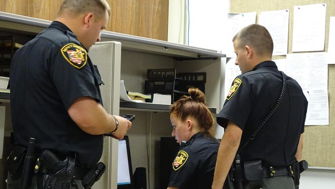 From left, deputies Brenton Davidson, Jenna Hornyak and Matt Kidwell exchange notes and information at the change between second and third shifts Friday night.