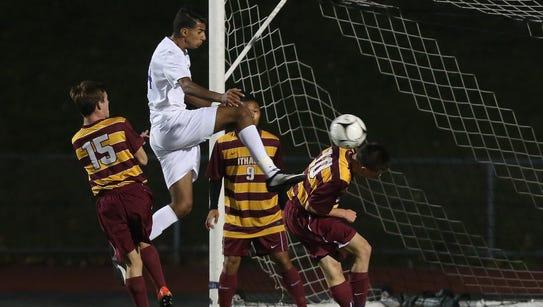 New Rochelle's (14) kicks the ball away from an Ithaca