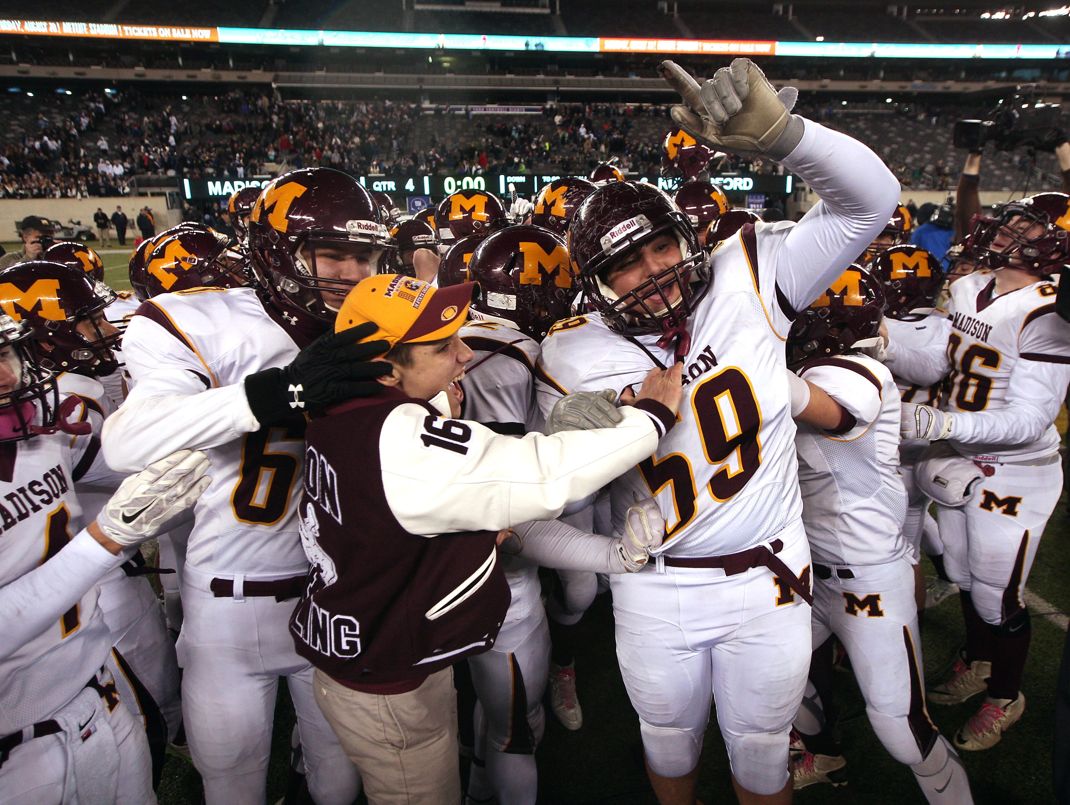 Madison's Yiakos Kostidakis (59) celebrates with his team after beating Rutherford in the North 2, Group 2 NJSIAA football Championship at MetLife Stadium. Madison won 27-6. December 3, 2015, East Rutherford, NJ.