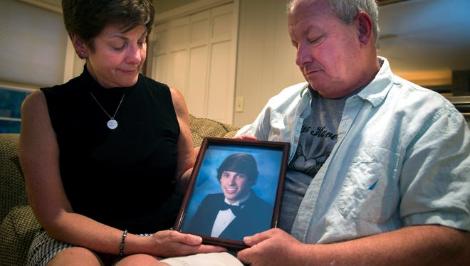 """Karen and Mark Witthauer pose for a portrait with an image of their son, Greg, at their home Thursday, July 12, 2018, in Franklin. """"The last time I saw him, I got to hug him and kiss him and tell him I loved him,"""" Karen Witthauer said with tears in her eyes. """"And that I believed in him and he would be all right."""" Greg Witthauer died of a drug overdose in April 2017 at the age of 23."""