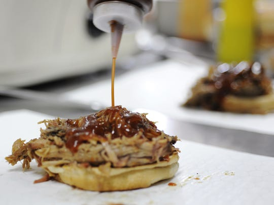 Homemade barbecue sauce is added to a brisket sandwich Friday at Johnson's Boucaniere in Lafayette.
