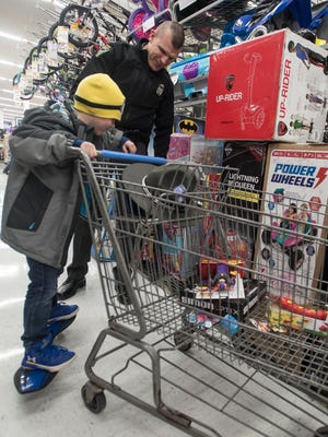 """Ohio State Trooper Adrian Wilson helps balance Cash Temple, 6, on a skateboard to see if he would like to get it as part of his Cash for Kids toy choice. """"I really like volunteering and doing it for the kids and seeing the joy in their faces,"""" said Wilson."""