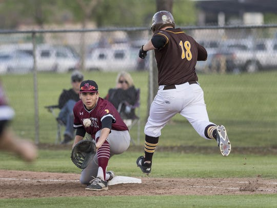 Mt. Whitney's Jordan Rojas takes a throw at first as Golden West's Bryson Johnson tries to get on base in a West Yosemite League high school boys baseball game on Thursday, March 23, 2017. Johnson was called out on the play.
