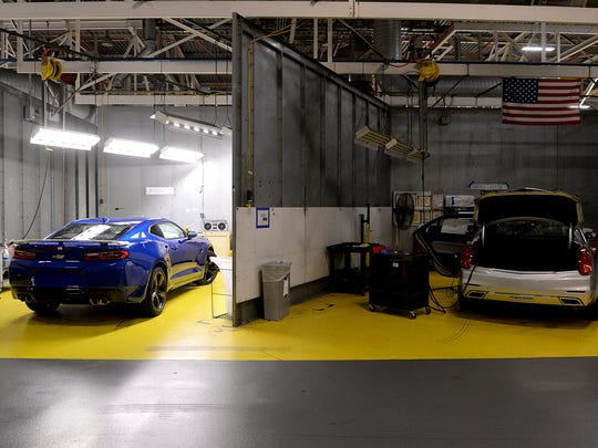 A new, blue 2016 Chevrolet Camaro sat in the body shop