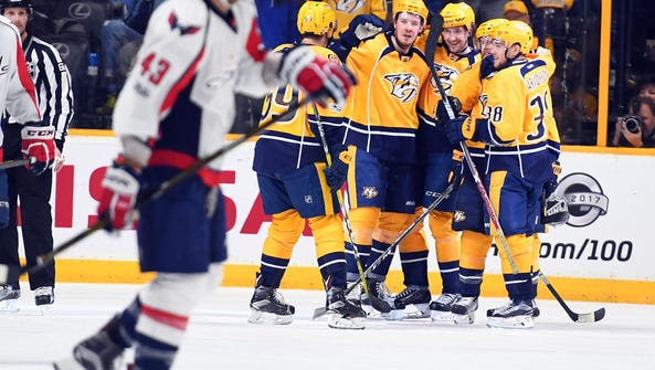 Predators players celebrate after a goal by left wing