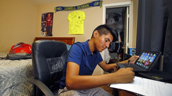 Juan Alvarado studies in his room with a iPad he is working to pay off on Nov. 2, 2016, in Phoenix.  Alvarado, a Foley scholarship recipient, attends Brophy College Preparatory school and is mentored by Eddie Martinez.