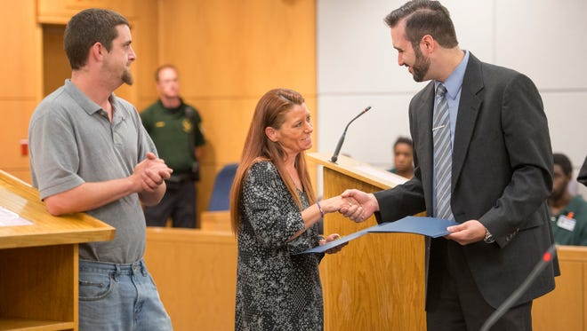 TEAM Court coordinator Matt Castagna, right, presents a certificate and inspirational coin to Farrah Merrittduring the TEAM Court graduation ceremony in Pensacola on Wednesday, May 10, 2017.