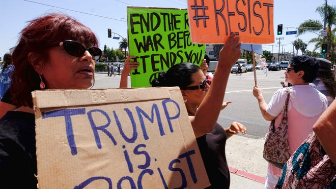 Demonstrators carrying signs in protest to racism walk along Main Street in the Venice beach area of Los Angeles on Saturday.