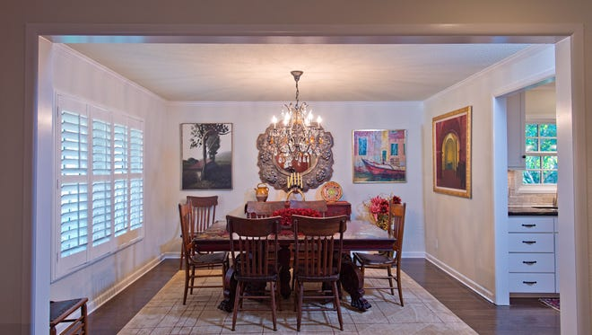 The hardwood floored formal dining area takes in plenty of natural light via a large plantation shuttered picture window illumninting colorful art
