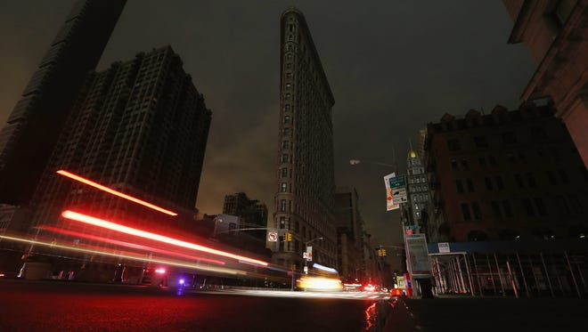 Cars are blurred as they pass a darkened Flatiron Building in a section of Manhattan in a blackout after Superstorm Sandy on Oct. 30, 2012.