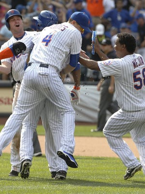 Daniel Murphy, left, Wilmer Flores (4) and relief pitcher Jenrry Mejia (58) celebrate with the Mets Juan Uribe, second from left, who hit a tenth-inning, walk-off single to lift the Mets to a 3-2 victory over the Los Angeles Dodgers.