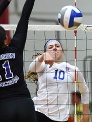 Reno senior Parker Buddy spikes the ball as McQueen's Sam Valele goes up for the block in the Tuesday's game at Reno.
