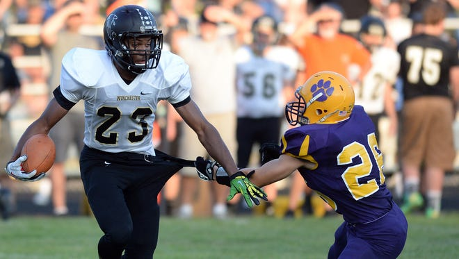 Winchester Community's Kiante Enis, left, broke the school record for rushing yards in a game with 392 yards on 17 carries against Hagerstown on Sept. 5, 2014.