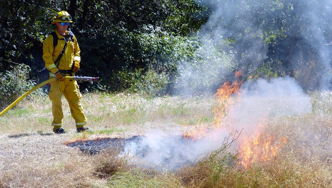 A firefighter watches over a grass fire that was started by fireworks during a demonstration Thursday.