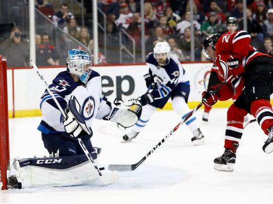 Devils right wing Stefan Noesen, right, scores a goal on Winnipeg Jets goalie Connor Hellebuyck (37) during the second period of a game, Tuesday, March 28, 2017, in Newark.
