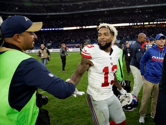 New York Giants wide receiver Odell Beckham (13) shakes hands with a camera man after an NFL football game between New York Giants and Los Angeles Rams at Twickenham stadium in London, Sunday Oct. 23, 2016. (AP Photo/Matt Dunham)