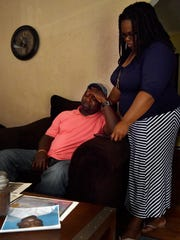 Lasonia Mangum, right, comforts Melvin Mangum as they look through photographs of their son at Lasonia's home in Jackson Wednesday. Melvin Mangum Jr. died at age 18, May 22.