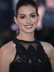 Anne Hathaway poses for photographers as she arrives