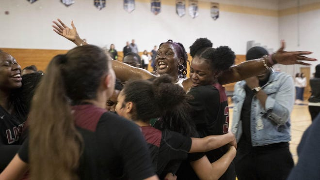 Palm Beach Lakes Rams head coach Cassandra Rahming celebrates with her team after the Rams 63-61 win over Boca Raton in the class 7A region 3 final in Boca Raton, Feb. 21, 2020.