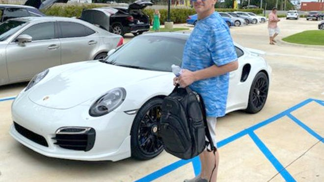 Casey William Kelley poses in front of a Porsche.