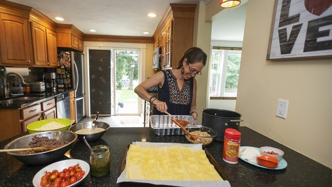 Shari McBurney, of Stoughton, begins her lasagna for Lasagna Love, with a layer of her homemade sauce made from roasted tomatoes that grew in her garden on Wednesday, Sept. 9, 2020.