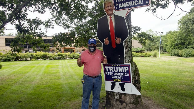 Bob Sullivan poses with a large Donald Trump cutout that is displayed outside of his company, Sullivans Inc., at Franklin Street and Route 27 in Hanson.