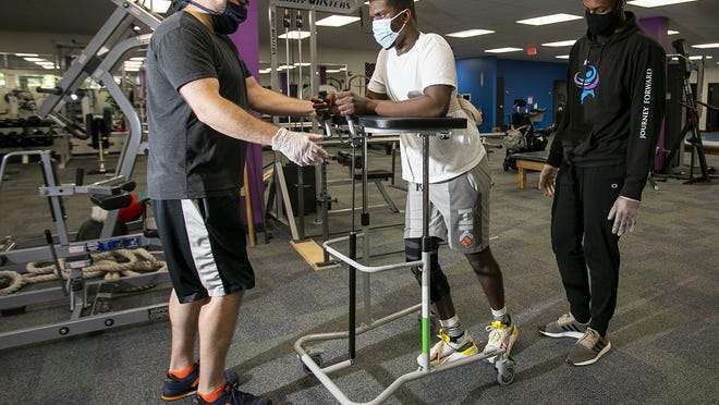 Jacques Matellus, 23, of Brockton practices walking as Neurological Exercise Therapists Mike Baker (left) and Garrison Duvivier (right) of Journey Forward in Canton spot him on Monday, June 15, 2020. Matellus is relearning how to walk after a freak accident nearly a year ago left him paralyzed from the neck down.