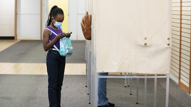 FILE - Kailah Billy, 8, of Brockton, plays on her phone as she waits for her mother to vote at the Westgate Mall polling station during early voting in the primary elections on Aug. 23, 2020.