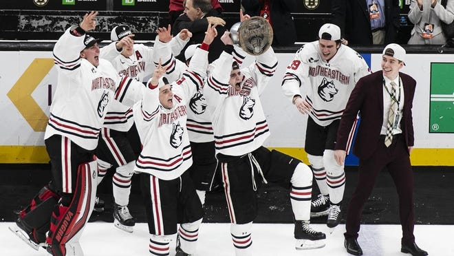 Northeastern's Ryan Shea of Milton holds up the Beanpot Cup to celebrate with teammates after defeating Boston University 5-4 in double overtime on Monday, Feb. 10, 2020 at the TD Garden in Boston.