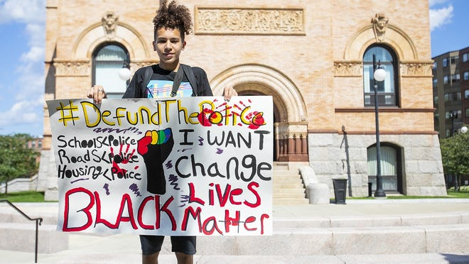 Denzel Gomes, 16, of Brockton holds a sign calling to defund the police outside Brockton City Hall on July 2, 2020. Gomes held his sign in protest in part to express opposing the recent city budget, which made cuts to the Brockton Public Schools.about a half-dozen other teens and a teacher joined him in the protest.