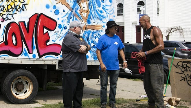 Plymouth County Sheriff Joe McDonald, Pastor Roberto Silveira of the Universal Missionary Church and artist Lee Soares of Providence talk after Soares finished painting the side of the box-truck Wednesday, July 22, 2020. Artists in recovery þÄúmade-overþÄù the Homeless Improvement Project truck with graffiti art, the next step is to convert the truck into a mobile shower and barbershop for the homeless of Brockton.