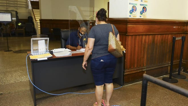 Brockton City Hall security guard Fabiola Garcon checks in visitors to City Hall on July 6, 2020. The city said it's getting reimbursement through the federal CARES Act for expenses attributed to the coronavirus pandemic, including plexiglass barriers, social distancing signage and security guards at City Hall.