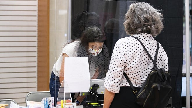 Volunteer Neena Farrar, 22, of Brockton checks a resident in at the Westgate Mall polling station on  Aug. 23, 2020 during the early voting period for the Sept. 1 state primary election.