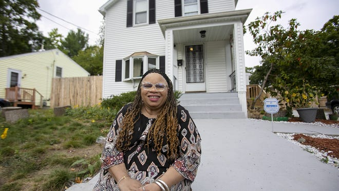 Denise Baker-Inegbenebo, of Brockton, sits in front of the home that once belonged to her grandparents at 121 Foster St. in Brockton on Sunday, Sept. 27, 2020. Her grandfather General H. Baker bought the home in the 1890s with his wife Nanny Baker, making them one of the first Black families in Brockton. General Baker was the deacon at Lincoln Congregational Church and Nanny Baker was the organist.